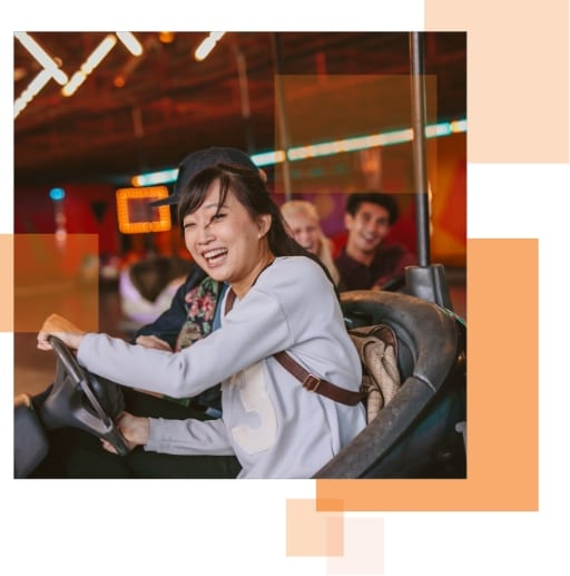 A woman and her friend riding bumper cars, enjoying the experience.