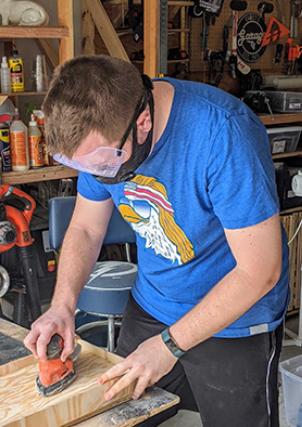 Devin sanding a piece of wood on his workbench