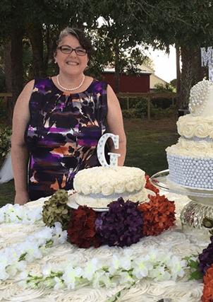 Dorothy next to cake she has decorated professionally